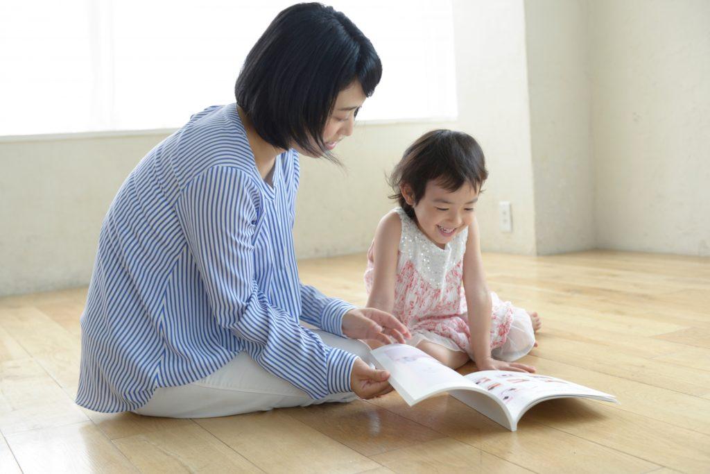 ママに本を読んでもらう女の子