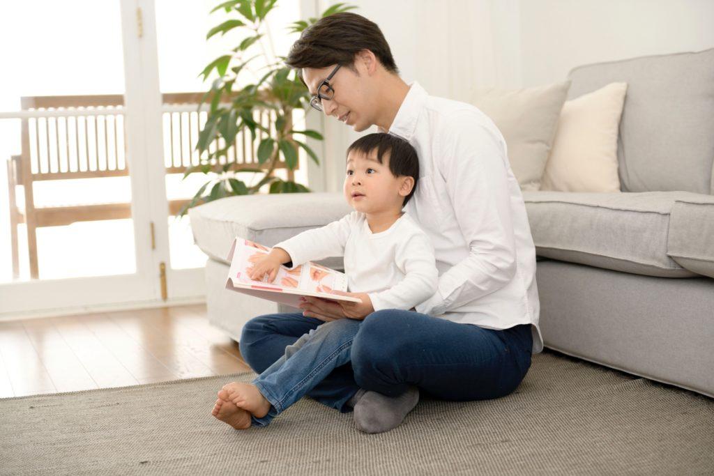 パパに本を読んでもらう男の子